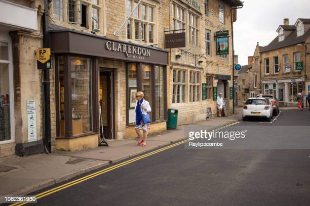 shoppers and tourists wandering around the market town of stow on the wold in the cotswolds - stow on the wold stock pictures, royalty-free photos & images