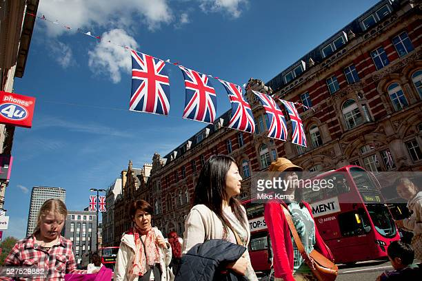 Shoppers and Union Jack flags in central London on Oxford Street UK This is the most famous street in the UK for shopping and mid range retail and is...