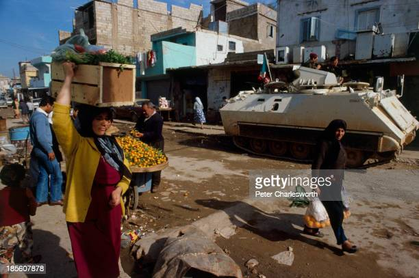 Shoppers and vendors in a war torn street in the Shatilla Palestinian refugee camp in Beirut's southern suburbs with an Italian armoured personel...