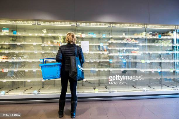 Shoppers are confronted with empty shelves at a supermarket that was raided by hoarders scared by the corona virus on March 14, 2020 in Wassenaar,...