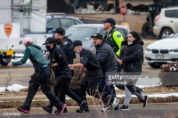 Shoppers are evacuated from a King Soopers grocery store after a gunman opened fire on March 22, 2021 in Boulder, Colorado. Dozens of police...