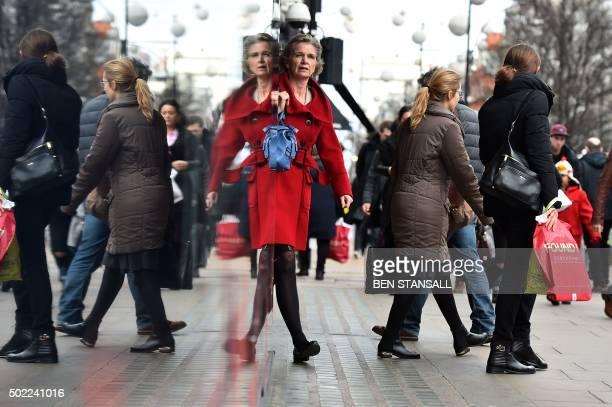 TOPSHOT Shoppers are reflected in a shop window as they walk along Oxford Street one of the main shopping streets in central London on December 22...