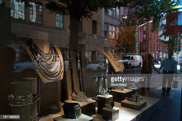 Shoppers are reflected in a window display in New York US on Wednesday Sept 18 2013 Consumers views of the US economic outlook deteriorated in...