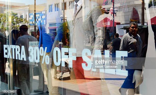 Shoppers are reflected in the window of a clothing store at the Third Street Promenade's outdoor shopping mall on August 17 2012 in Santa Monica...