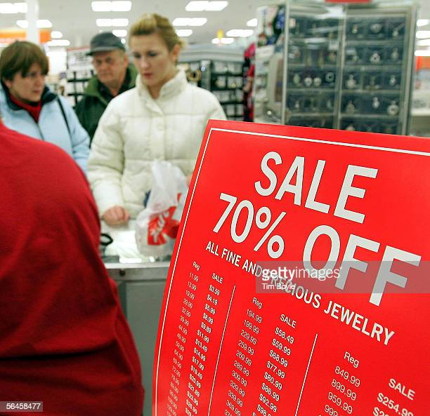 Shoppers are seen beyond a sale sign at the jewelry counter in a Kmart store December 19 2005 in Norridge Illinois Consumers are visiting stores in...