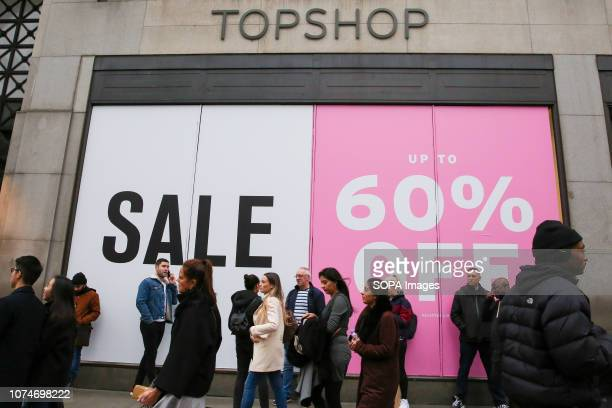 Shoppers are seen standing in front of a large SALE sign at the Topshop store window on London's Oxford Street. Last minute Christmas shoppers take...
