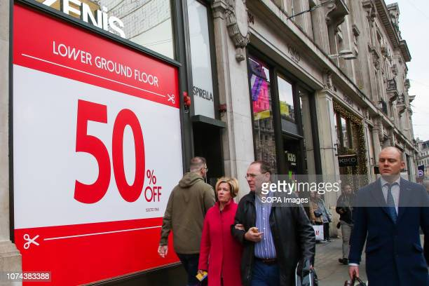 Shoppers are seen walking by a Tezenis sales sign on London's Oxford Street with 6 days to Christmas Day Retailers are expecting a rush of shoppers...