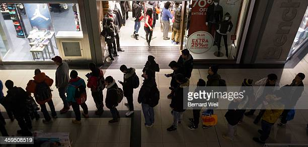 TORONTO ON DECEMBER 26 Shoppers are silhouetted by store lights as they wait for Foot Locker to open at 7am in Eaton Centre during Boxing Day...