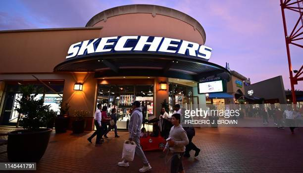 Shoppers at an outket mall walk past a Skechers store on May 21, 2019 in Los Angeles, California. - More than 170 shoe companies and retailers,...