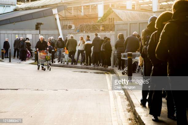 Shoppers at the Camden Sainsbury's store line up outside on March 21 2020 in London United Kingdom Coronavirus has spread to at least 186 countries...