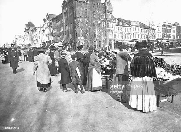 Shoppers at the outdoor food market 7th Street at Pennsylvania Avenue NW Washington DC Looking up 7th Street ca 1900