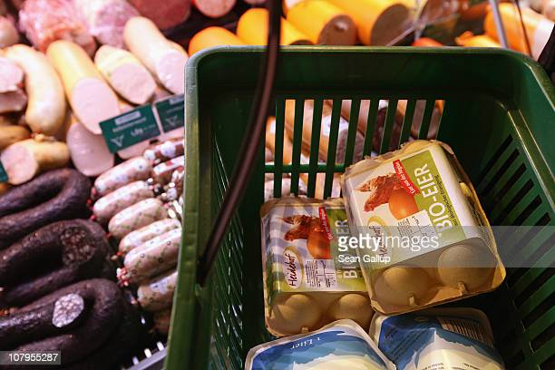 A shopper's basket contains cartons of organic chicken eggs next to a display of organic sausage at a branch of German organic grocery store chain...