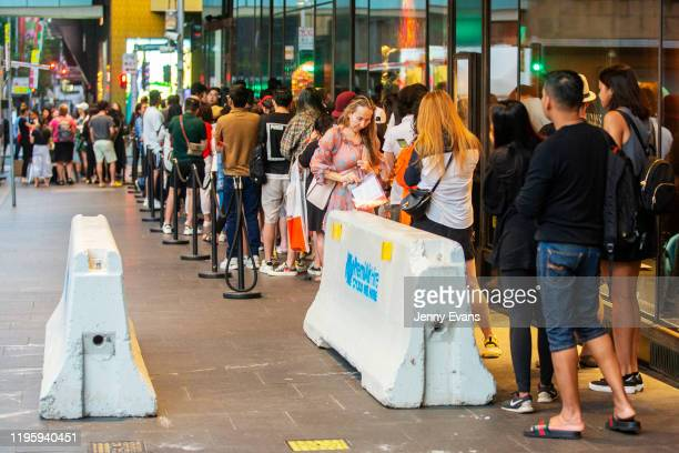 Shoppers behind barricades are seen waiting in line for the David Jones Elizabeth Street store to open at 6am on December 26 2019 in Sydney Australia...