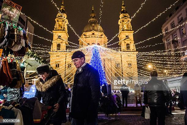 Shoppers browse alpaca wool products at a Christmas market as an illuminated Christmas tree stands in front of St Stephen's Basilica in Budapest...