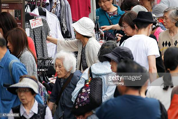Shoppers browse at a clothing store in a shopping street in the Sugamo district of Tokyo Japan on Sunday May 24 2015 Japan's Topix index fell for the...