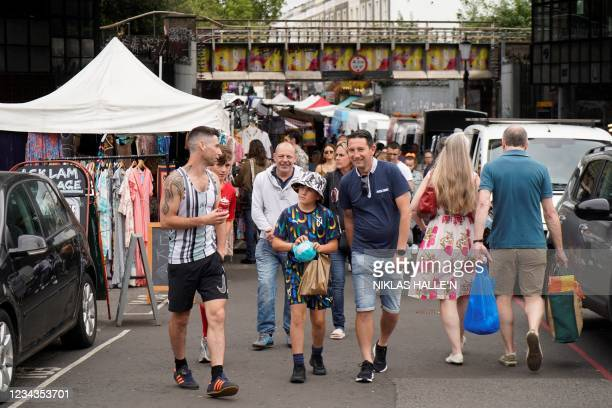 Shoppers browse at Portobello Road market in Notting Hill, west London on July 31, 2021. - Coronavirus case numbers increased more than 15 percent...
