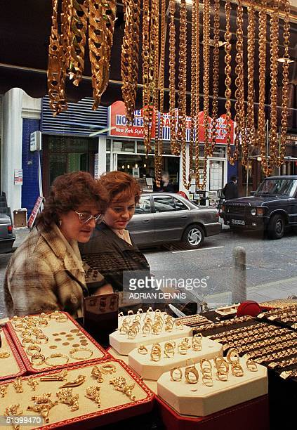 Shoppers browse at the jewellery in the window of a goldsmiths in Hatton Garden in London, 28 September 1999. The price of gold rose by nearly four...