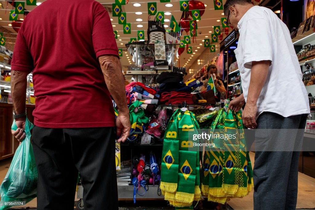 Shoppers browse Brazilian themed scarves ahead of the FIFA World Cup games in downtown Sao Paulo, Brazil, on Wednesday, June 13, 2018. In a curious quirk of Brazil's electoral calendar, for the last 28 years Latin America's largest economy has gone to the polls shortly after the World Cup. In the football-obsessed country, politicians have long attempted to hijack the sport to burnish their image. Photographer: Patricia Monteiro/Bloomberg via Getty Images
