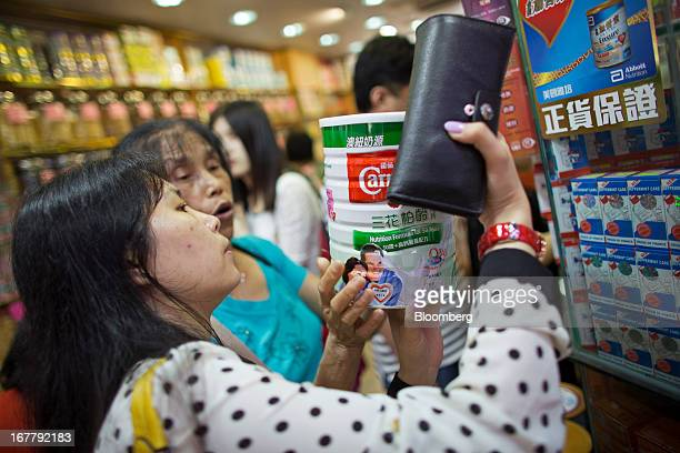 Shoppers browse cans of baby formula displayed in a pharmacy in the Mongkok district of Hong Kong China on Tuesday April 30 2013 Financial Secretary...
