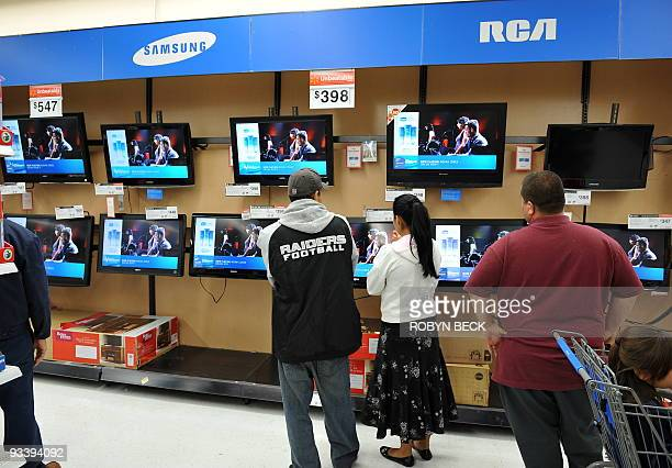 Shoppers browse flatscreen televisions at a Walmart store in Los Angeles California on November 24 a few days before Black Friday Major retailers...