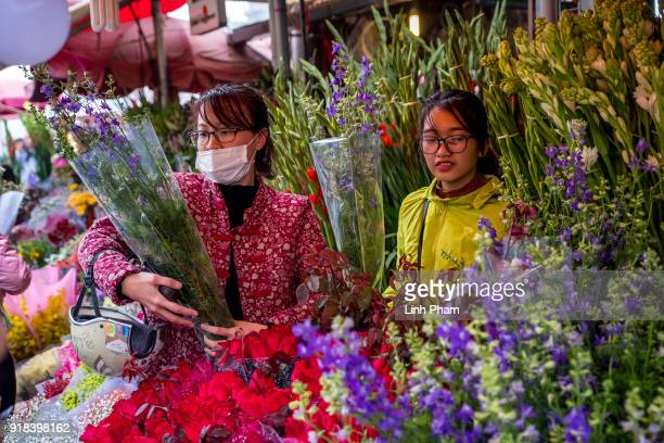 Shoppers browse flowers at Quang Ba flower market a favorite shopping place for local people for the Lunar New Year on February 14 2018 in Hanoi...
