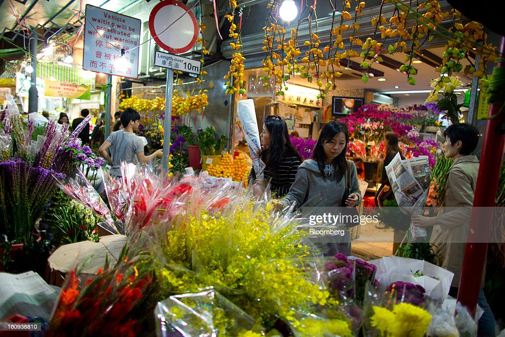 Shoppers browse flowers displayed for sale for the Lunar New Year on Flower Market Road in the Mongkok district of Hong Kong, China, on Thursday, Feb. 7, 2013. Hong Kong's stock market will be shut for three days next week for the Lunar New Year holidays, while markets in mainland China will be closed for the whole week. Photographer: Lam Yik Fei/Bloomberg via Getty Images