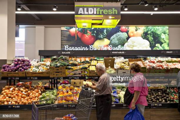 Shoppers browse foods in the produce department at an Aldi Stores Ltd food market in Chicago Illinois US on Tuesday Aug 1 2017 Aldi known for low...