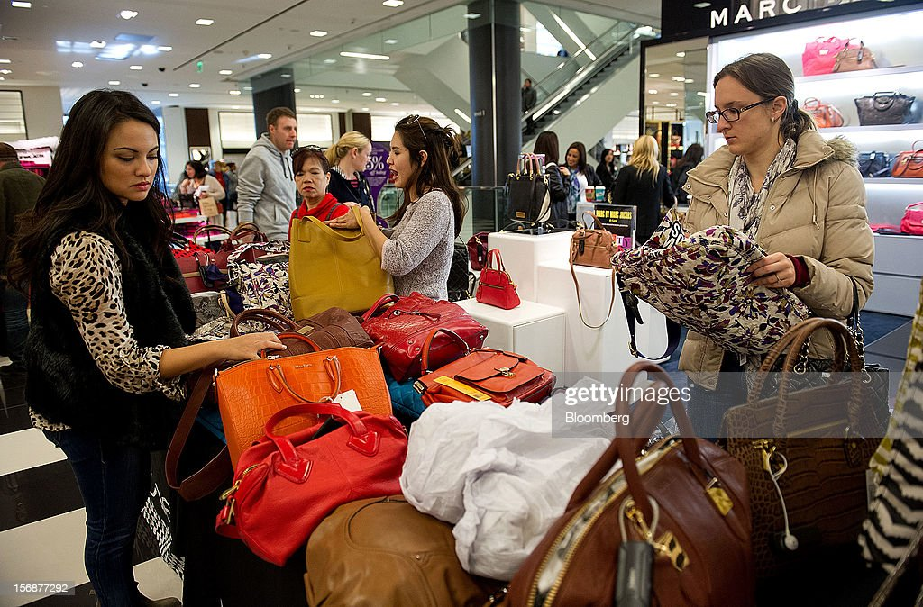 Shoppers browse handbags on sale at a Bloomingdale's store in the Westfield San Francisco Centre in San Francisco, California, U.S., on Friday, Nov. 23, 2012. To get shoppers to spend more than last year, retailers have continued to turn Black Friday, originally a one-day event after Thanksgiving, into a week's worth of deals and discounts. Photographer: David Paul Morris/Bloomberg via Getty Images