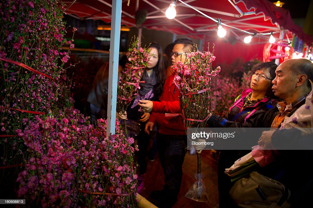Shoppers browse peach blossoms displayed for sale for the Lunar New Year in the Mongkok district of Hong Kong, China, on Thursday, Feb. 7, 2013. Hong Kong's stock market will be shut for three days next week for the Lunar New Year holidays, while markets in mainland China will be closed for the whole week. Photographer: Lam Yik Fei/Bloomberg via Getty Images