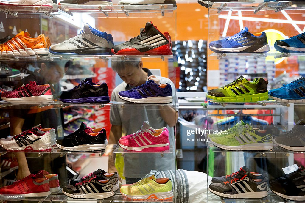 Shoppers browse running shoes inside a store at Lok Fu Plaza, operated by the Link Real Estate Investment Trust (REIT), in Hong Kong, China, on Monday, Nov. 10, 2014. The Link REIT, Asia's largest property trust which owns neighborhood malls, food markets, and car parks, is scheduled to announce interim results on Nov. 13. Photographer: Brent Lewin/Bloomberg via Getty Images
