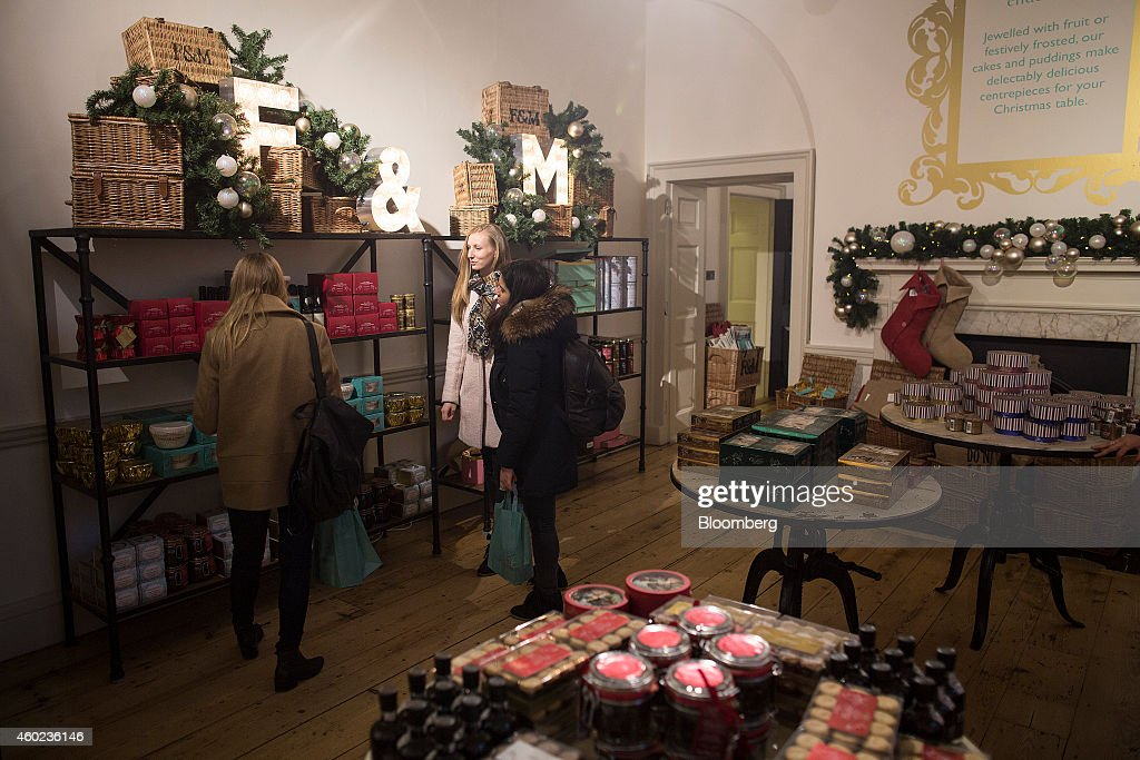 Shoppers browse specialty teas and festive foods displayed for sale inside a pop-up store, operated by Fortnum & Mason Plc, during a seasonal Christmas event at Somerset House in London, U.K., on Tuesday, Dec. 9, 2014. The British will be the biggest spenders in Europe on Christmas gifts this year, according to a study commissioned by Dutch bank ING Groep NV. Photographer: Simon Dawson/Bloomberg via Getty Images