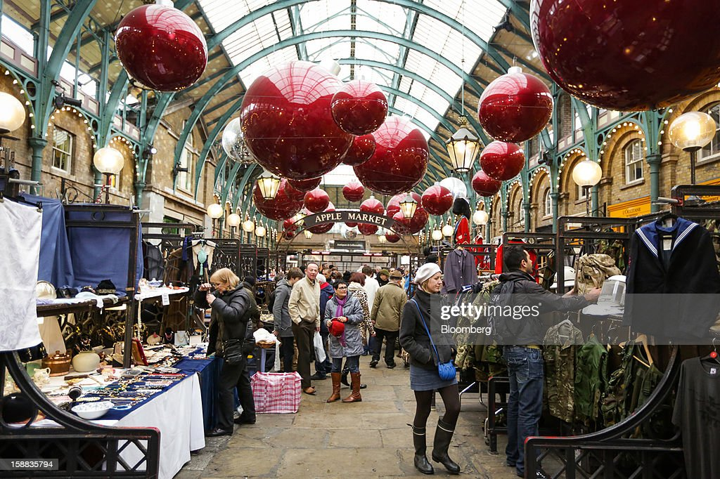 Shoppers browse stalls at a covered market in the Covent Garden district of London, London, U.K., on Monday, Dec. 31, 2012. The number of Britons making shopping trips for post-holiday bargains barely increased on the day after Christmas as more people sought discounts online. Photographer: Jason Alden/Bloomberg via Getty Images