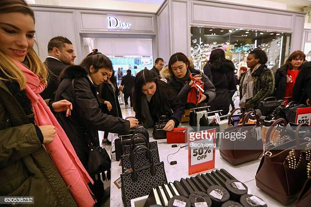 Shoppers browse the ladies handbags on sale in Selfridges Plc department store during the Boxing Day sales in London UK on Monday Dec 26 2016...