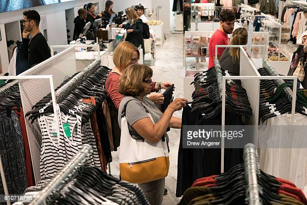 Shoppers browse the racks at an HM clothing store on Fifth Avenue September 27 2016 in New York City In September consumer confidence rose to its...