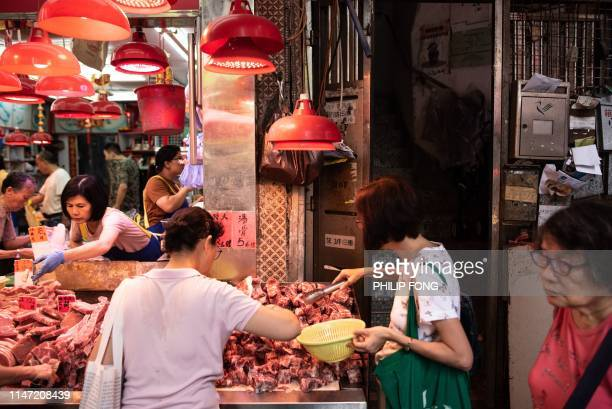 Shoppers buy frozen meat at a stall after fresh pork sold out at a market in the Mong Kok district in Hong Kong on June 1 2019 Hong Kong will cull...