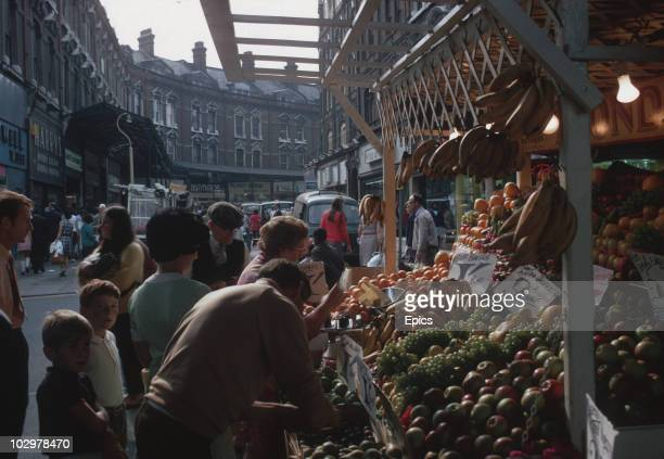 Shoppers buy fruit from a stall on Brixton market London October 1970