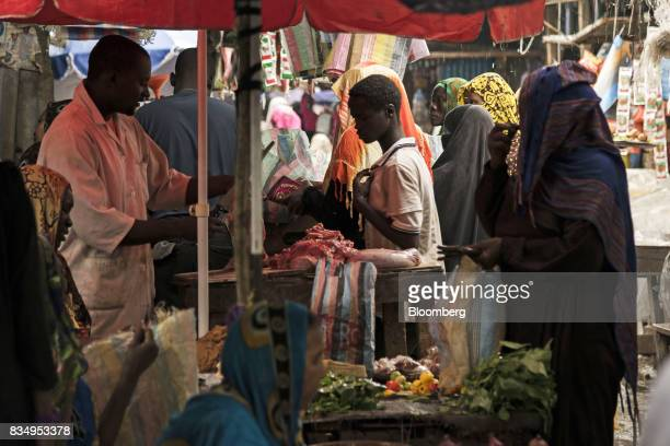 Shoppers buy goods from a food vendor in an outdoor market in N'Djamena Chad on Tuesday Aug 15 2017 African Development Bank and nations signed...
