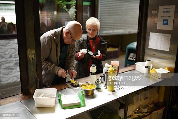 Shoppers buy hot black pudding from a stall in the open section of Bury Market in Bury northern England on August 5 2015 Bury Market which has over...