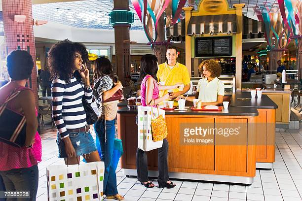 Shoppers buy snacks at a mall coffee stand