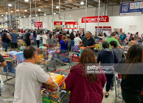 Shoppers buy toilet paper food and water at a store as people begin to panic buy and stockpile essentials from fear that supplies will be affected by...