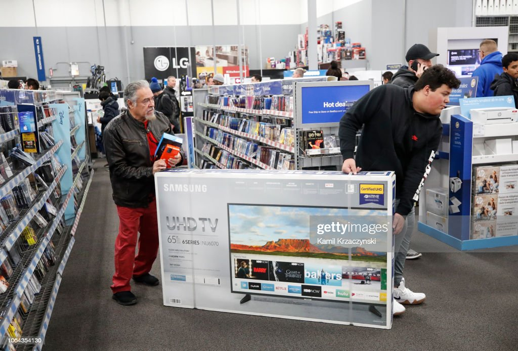 Shoppers Carry A Flat Screen Tv Through A Best Buy Inc Store On