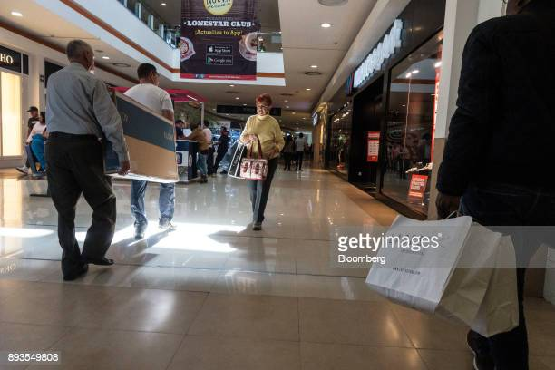 Shoppers carry a Samsung Electronics Co High Definition Television at the Forum Buenavista mall in Mexico City Mexico on Monday Nov 20 2017 The...