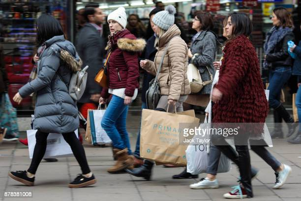 Shoppers carry bags along Oxford Street on November 24 2017 in London England British retailers offer deals on their products as part of the annual...