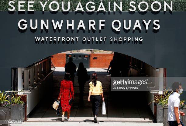Shoppers carry bags as they leave after visiting recently re-opened shops at Gunwharf Keys shopping centre in Portsmouth, southern England on June...