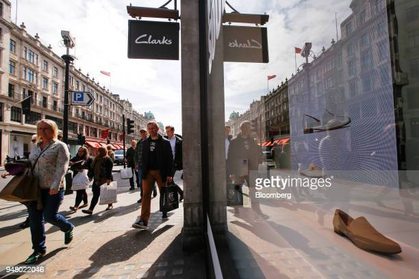 Shoppers carry bags as they pass Clarks shoe shop operated by C J Clark Holdings Ltd on Regent Street in London UK on Tuesday April 17 2018 While...