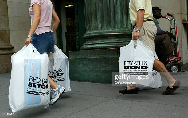 Shoppers carry bags from a Bed Bath & Beyond store June 27, 2003 in New York City. The home goods retailer announced June 26, 2003 that it sees as...