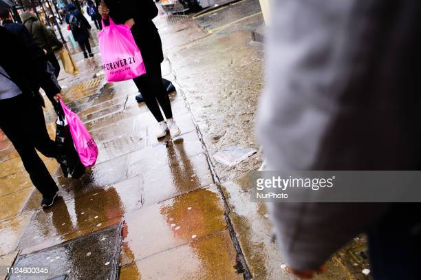 Shoppers carry bags from clothing retailer Forever 21 along Oxford Street on a wet afternoon in London England on February 8 2019 February 15 sees...