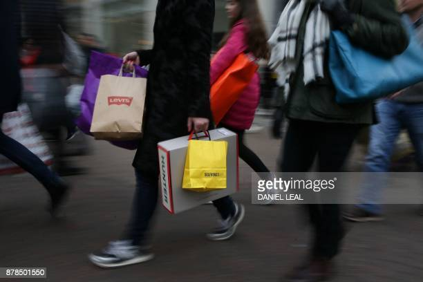 Shoppers carry bags from retailers including Levi's and Selfridge's as they walk along Oxford Street in London on November 24 2017 Black Friday is a...