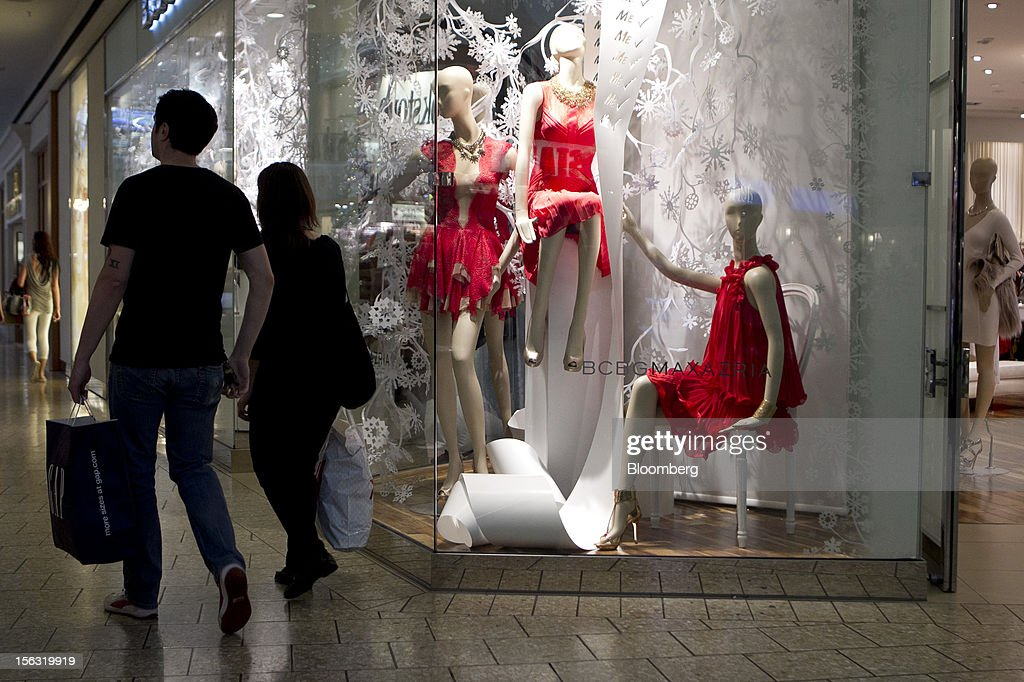 Shoppers carry bags while passing in front of a BCBG MAX Azria Group Inc. store at the Fair Oaks Mall in Fairfax, Virginia, U.S., on Monday, Nov. 12. 2012. Sales at U.S. retailers probably fell in October for the first time in four months economists said before a report on Nov. 14. Photographer: Andrew Harrer/Bloomberg via Getty Images