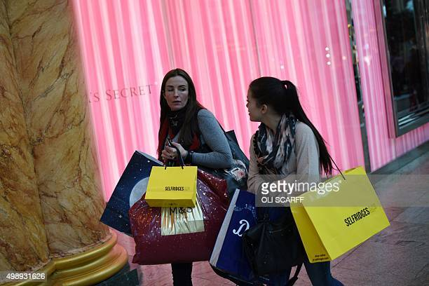 Shoppers carry bundles of shopping bags as they walk through the Trafford Centre shopping mall past retailers offering 'Black Friday' discounts in...